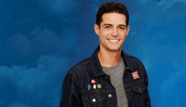Wells Adams smiles in a denim jacket while posing against a blue background.