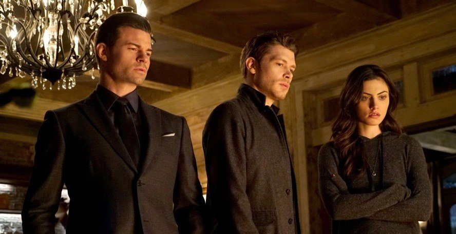 Elijah, Klaus, and Hayley stand together in a room looking down on The Originals.