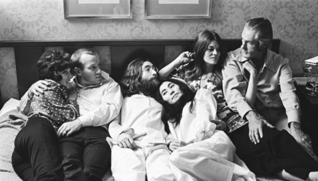 John Lennon, Timothy Leary, Yoko Ono, Tom Smothers, Rosemary Woodruff Leary lie down on a bed.