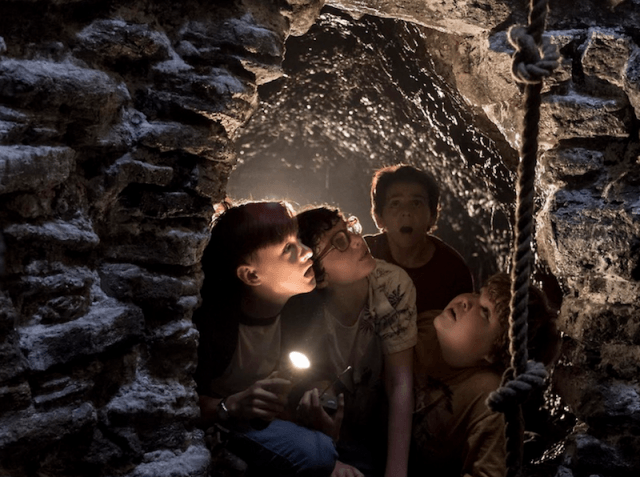 A group of kids looks up at a rope.