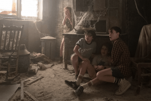 A group of kids huddle in a corner of an abandoned house.