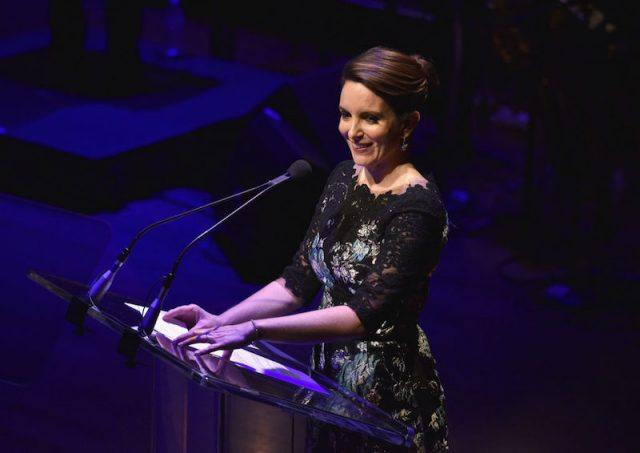 Tina Fey stands in front of a podium while speaking to an audience.