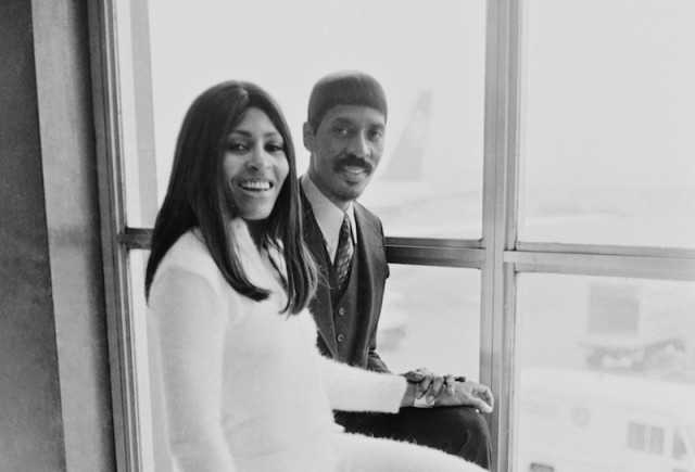 Ike and Tina Turner stand in front of a window and smile.