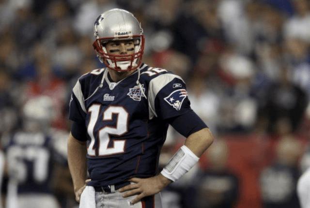 Tom Brady stands on a football field.