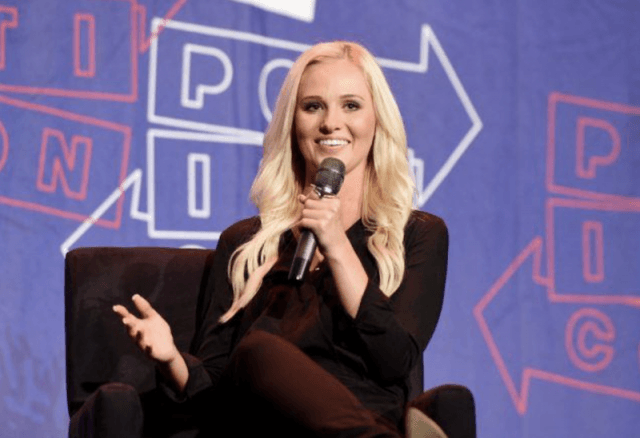 Tomi Lahren speaking into a microphone while sitting on a black chair.