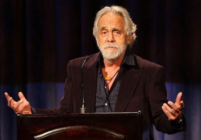 Tommy Chong holds his hands up while speaking at an event in Beverly Hills.