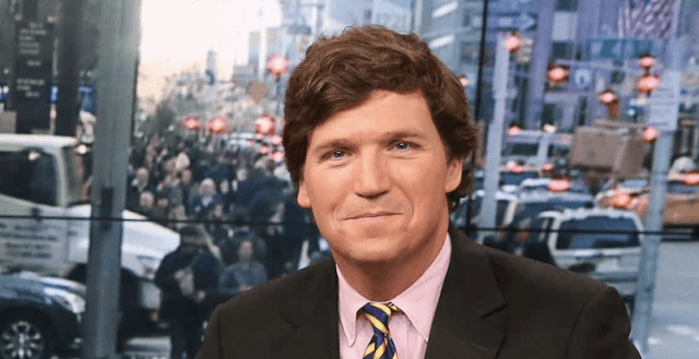 Tucker Carlson sitting at a news desk in front of a clear glass window in New York City.