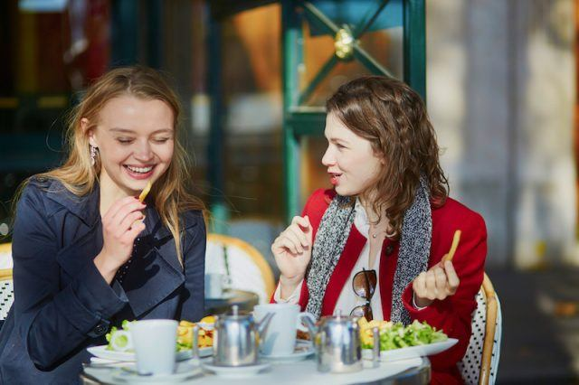 Two friends enjoying an outdoor lunch together.