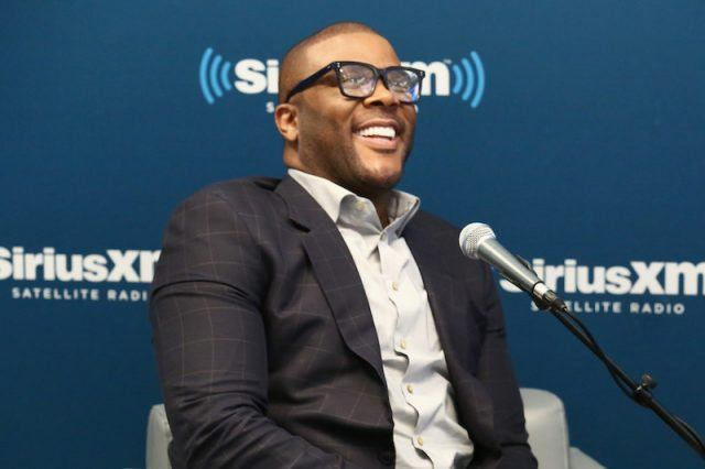 Tyler Perry in a black suit talking in front of a mic.
