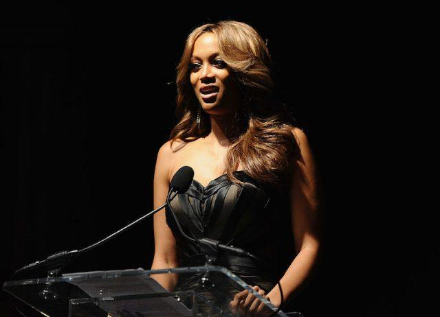 Tyra Banks speaks at a podium in a black gown.
