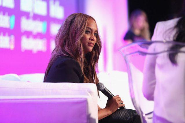 Tyra Banks sits on a couch during a panel and holds a microphone.