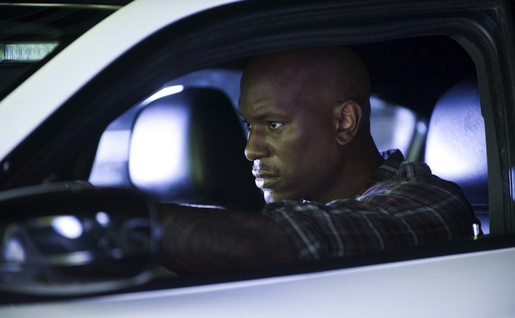 Tyrese Gibson looks ahead while driving a car