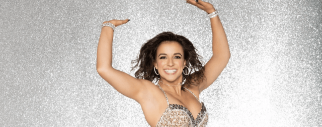 Victoria Arlen poses with her hands over her head and smiling.