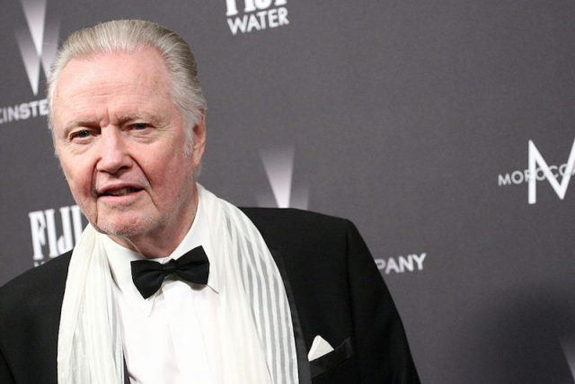 Voight wearing a tuxedo and posing on a red carpet.
