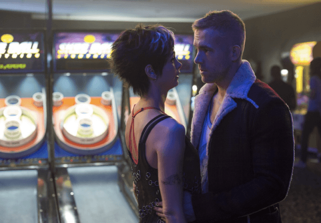 Wade and Vanessa in a bar/arcade looking at each other.
