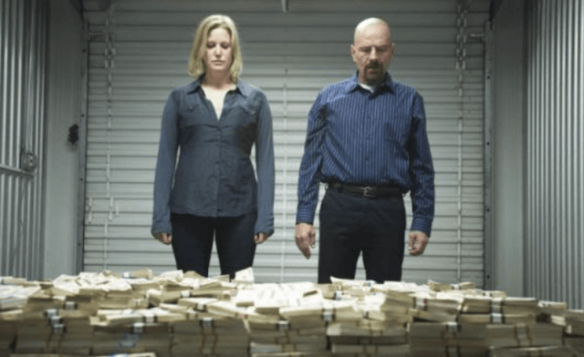 Walter & Skyler standing in front of stacks of money.
