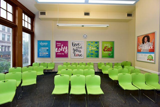 A Weight Watchers meeting room with posters and bright green chairs.