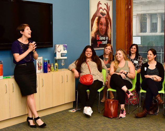 A weight watchers workshop or meeting taking place with a speaker welcoming guests.