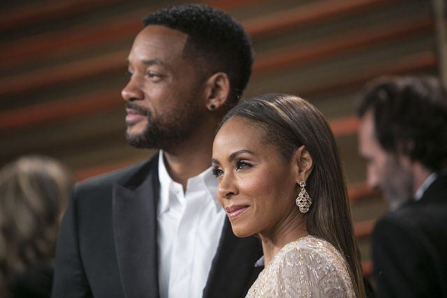 Will Smith and Jada Pinkett Smith pose together on a red carpet and look forward as they smile slightly.