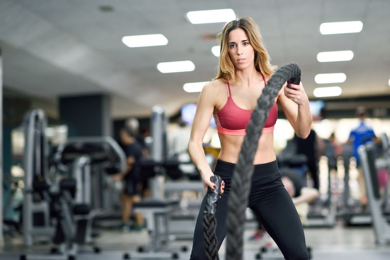a woman working out with a rope in the gym