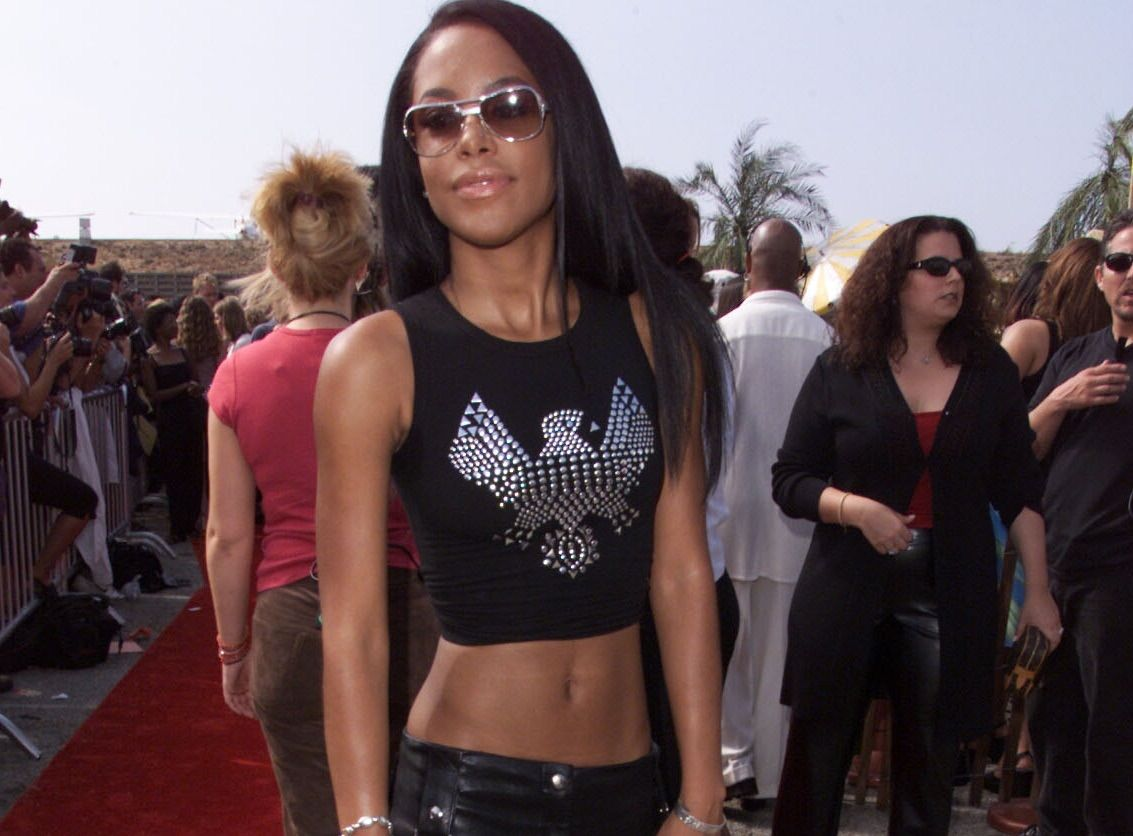 Aaliyah poses at an event in a crop top and black pants