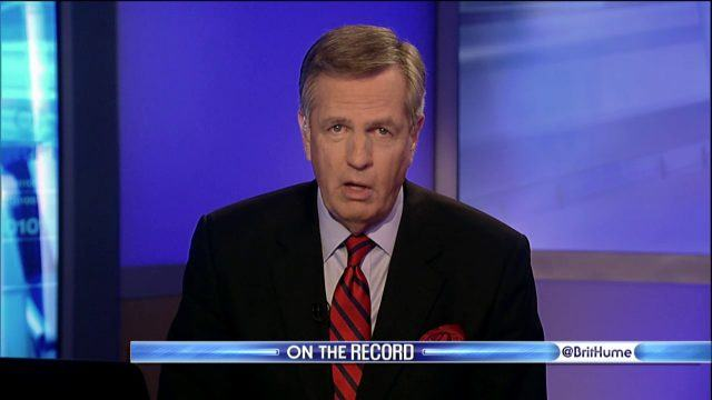 Brit Hume reporting behind a news desk in a red and black striped tie and black suit.