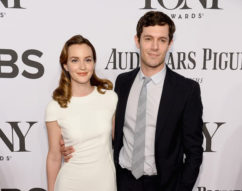 Leighton Meester and Adam Brody pose on the red carpet with their arms around each other.