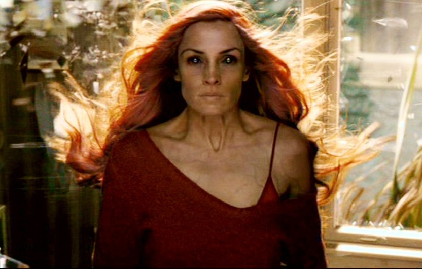 Jean Grey looks straight ahead while her red hair blows in the window