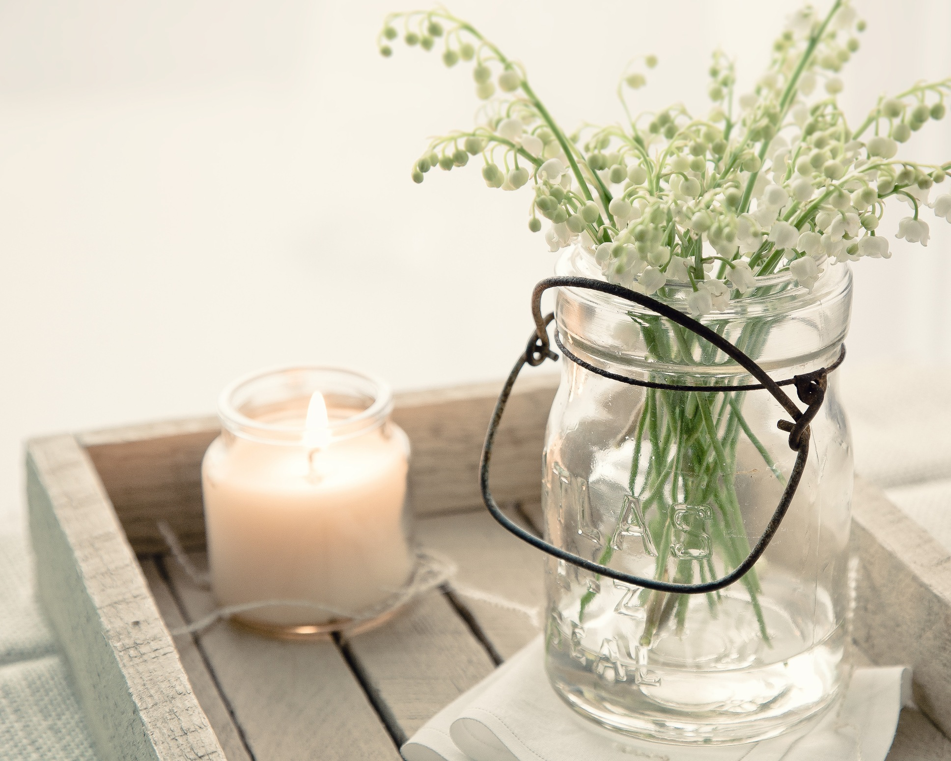 A plant and a candle on a wooden tray