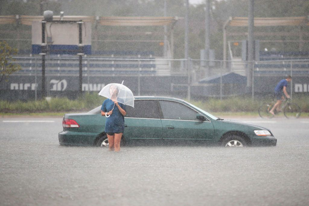 A woman with an umbrella walks from her car in a flooded street.