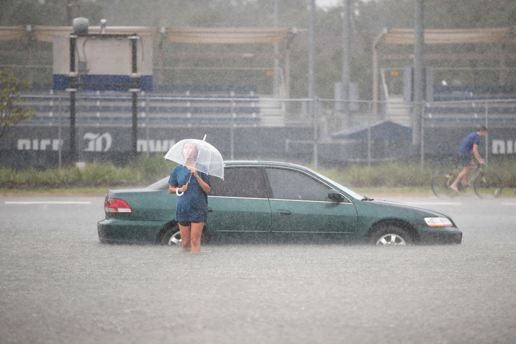 Woman with umbrella walks through water from her car in a steady rain.
