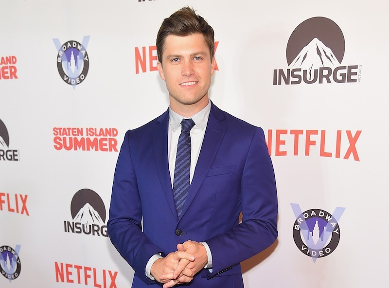 Colin Jost poses in a blue suit at a Netflix event