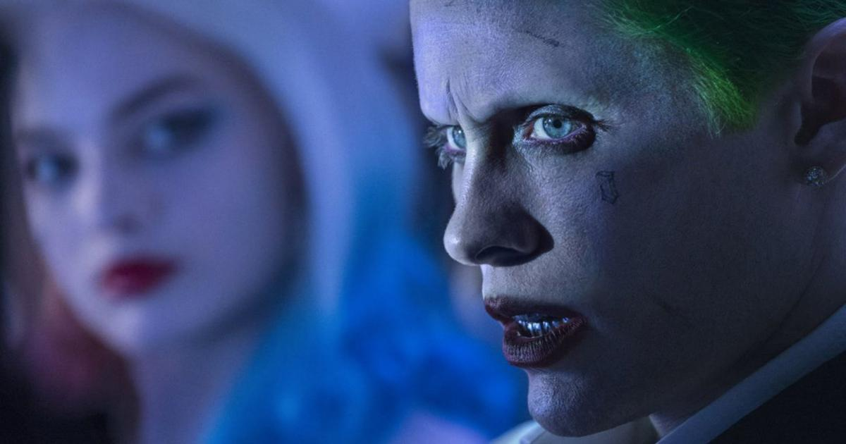 The Joker looks angry while Harley Quinn faces him in the passenger seat