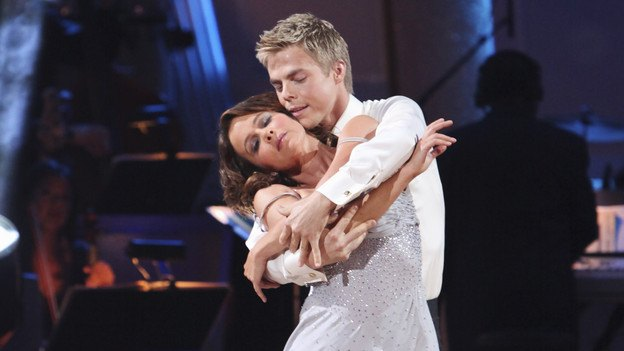Jennifer Grey and Derek Hough embrace while dancing in white costumes on Dancing with the Stars