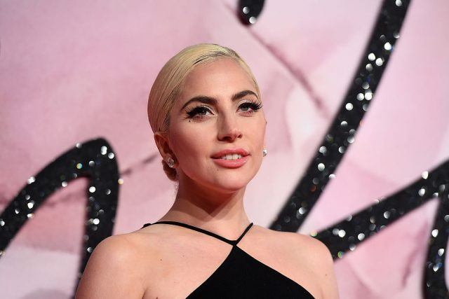 Lady Gaga posing in a black dress in front of a pink and black background.