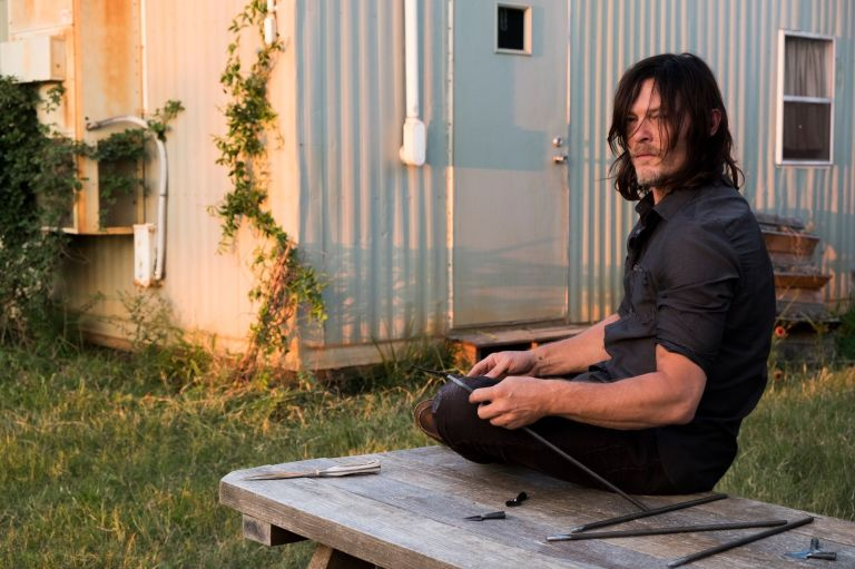 Daryl sits on a bench in front of a trailer holding a tool