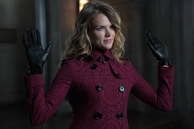 Barbara holds up her hands while wearing a Burgundy coat