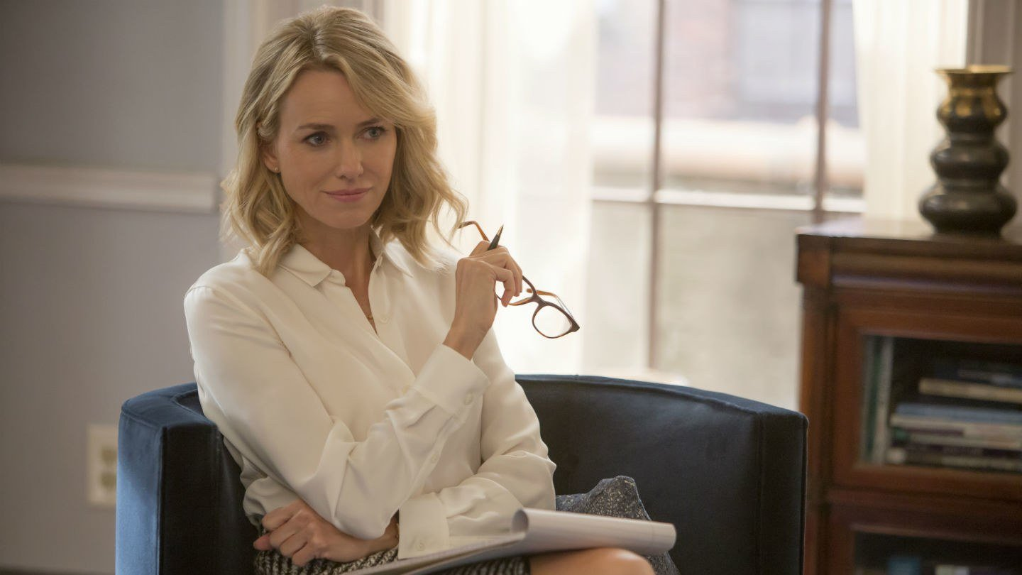 Naomi Watts sits on a couch and holds glasses