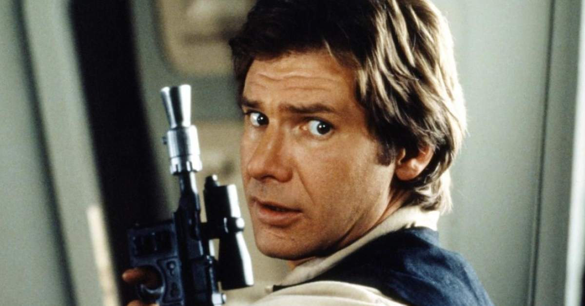 Harrison Ford holds a weapon and looks over his shoulder Han Solo