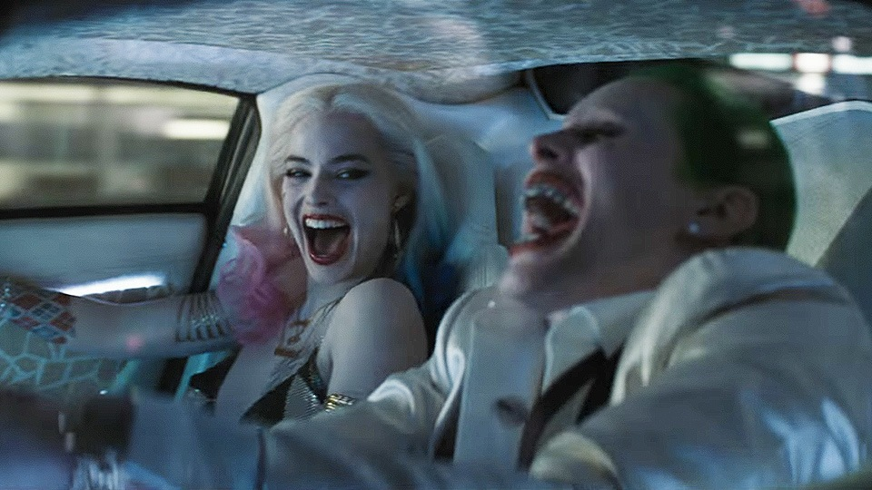 Harley Quinn and the Joker laugh while riding in a car