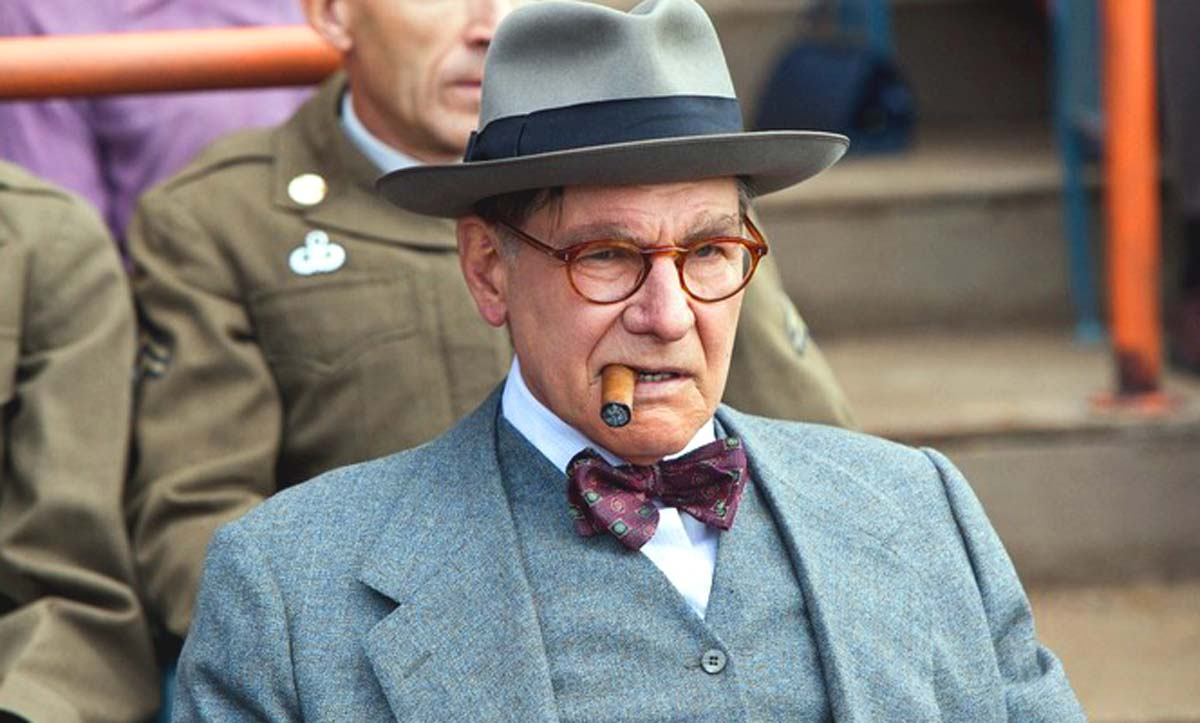 Harrison Ford wears a suit and fedora and smokes a cigar as Branch Rickey in 42