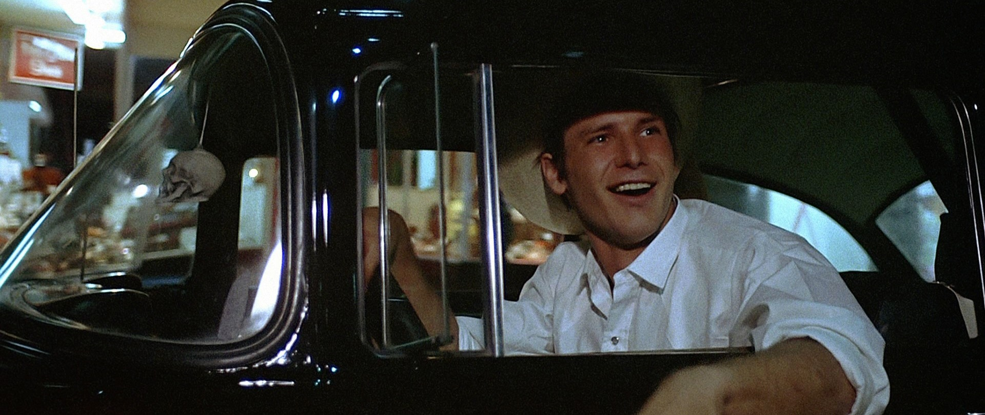 Harrison Ford sits in the driver's seat as Bob Falfa in American Graffiti