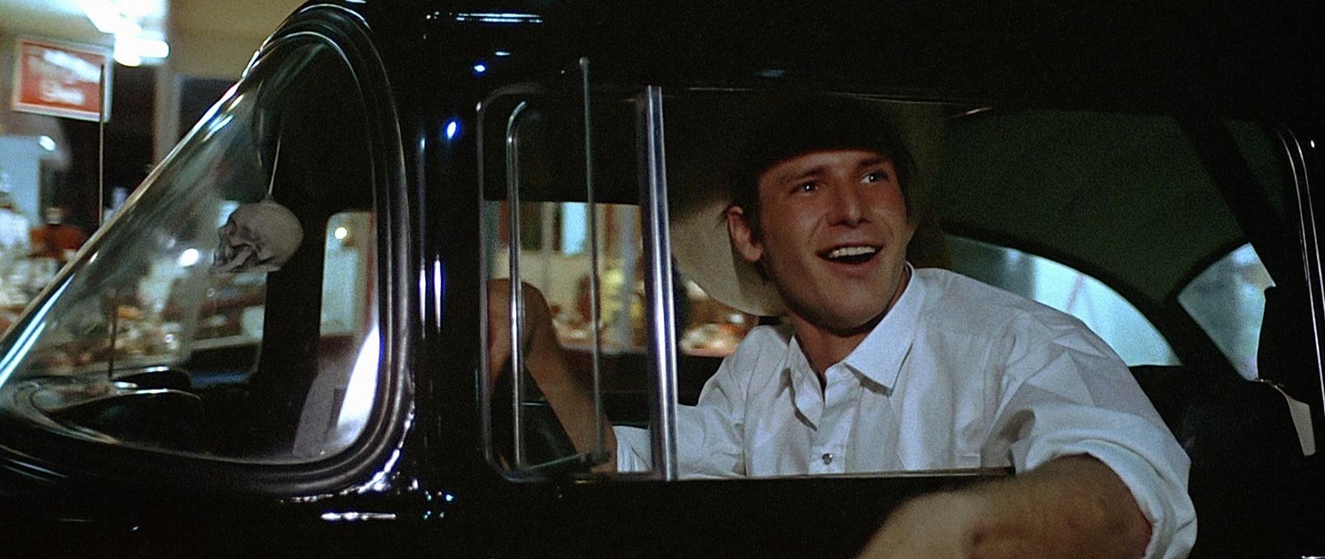 Harrison Ford sits in the driver's seat as Bob Falfa in American Graffiti