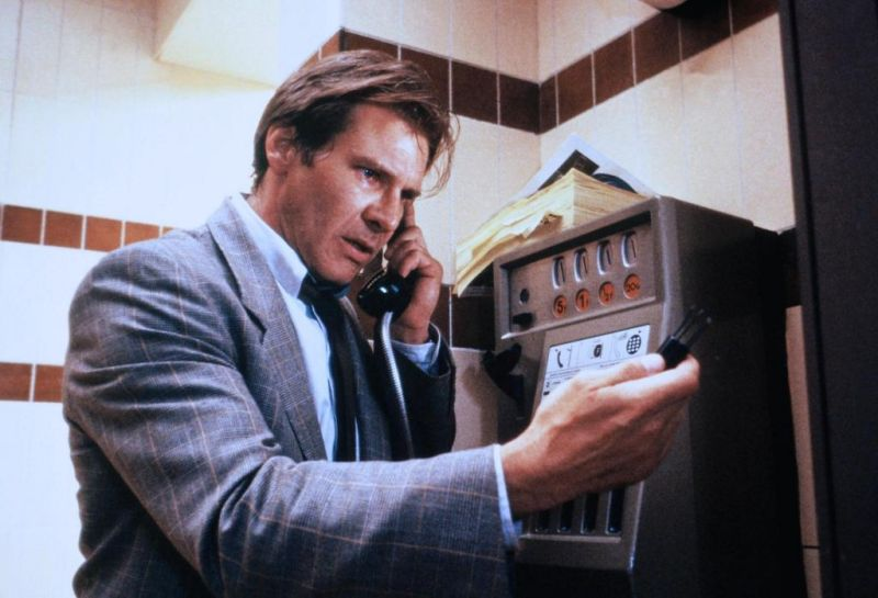 Harrison Ford holds a phone to his ear and looks at an item in his hand as Dr. Richard Walker in Frantic