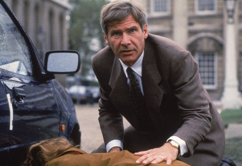 Harrison Ford crouches near a car in a suit as Jack Ryan in Patriot Games
