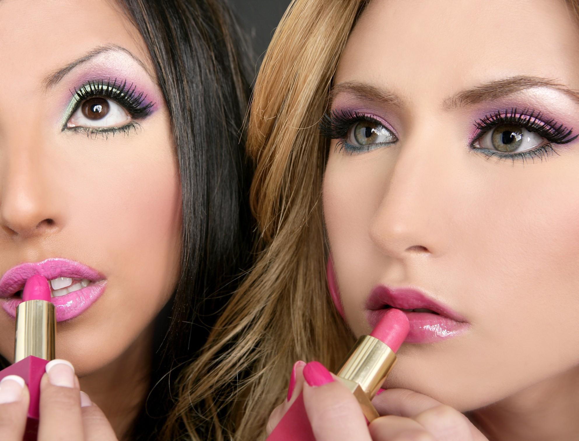two women in heavy makeup applying lipstick