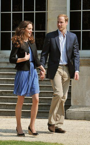 Kate Middleton and Prince William walking together as they hold hands.