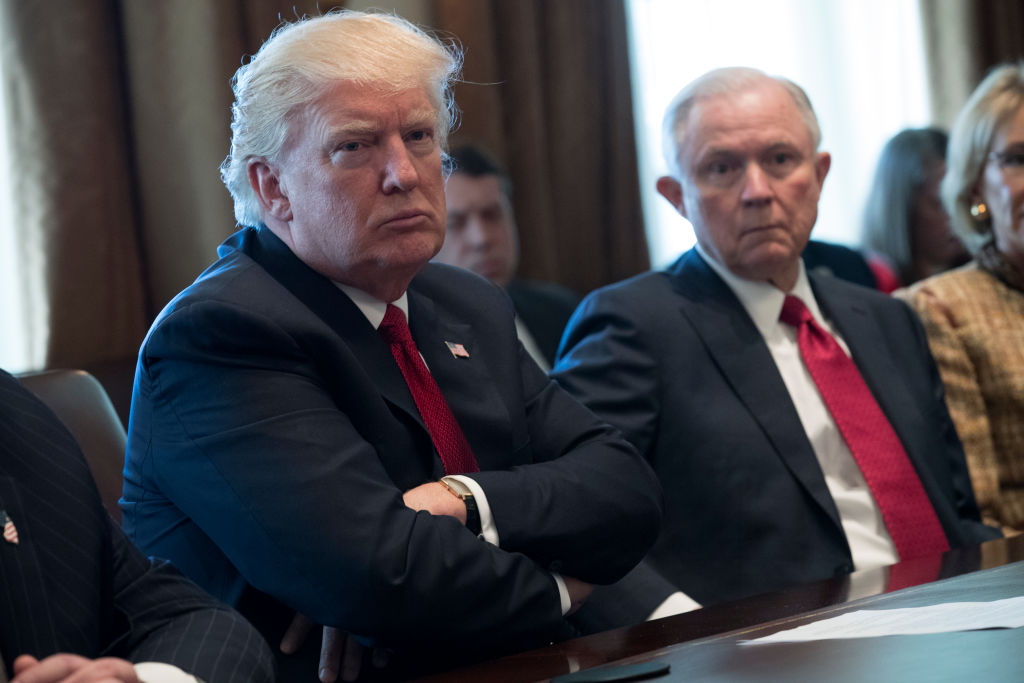 Donald Trump with his arms folded, sitting next to Attorney General Jeff Sessions