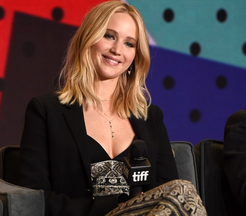 Jennifer Lawrence smiles while wearing a black blazer and holding a microphone
