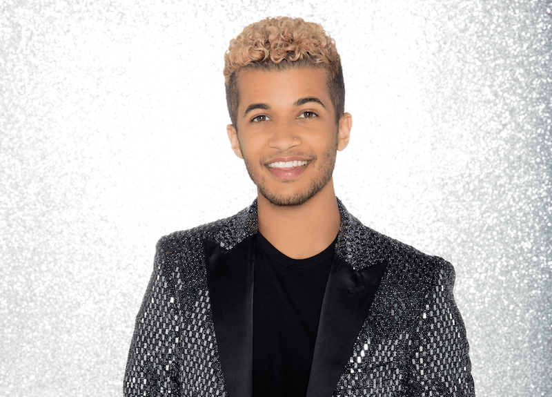 Jordan Fisher poses in a black rhinestone blazer